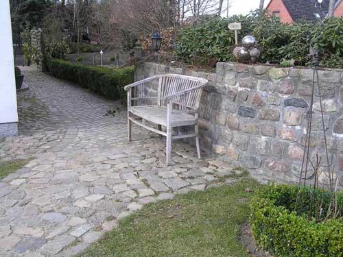 In Verbindung von Natursteinmauer und Weg entstand hier ein sonniger Platz für die kurze Pause zwischendurch.
