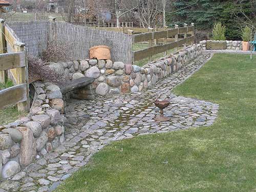 Gartengestaltung mit Steinen - Rustikale Sitzgelegenheit im hinteren Teil des Gartens.