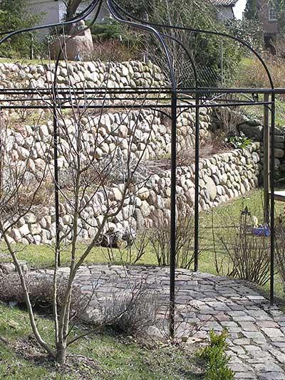 Natursteinmauer am Hang aus Feldsteinen