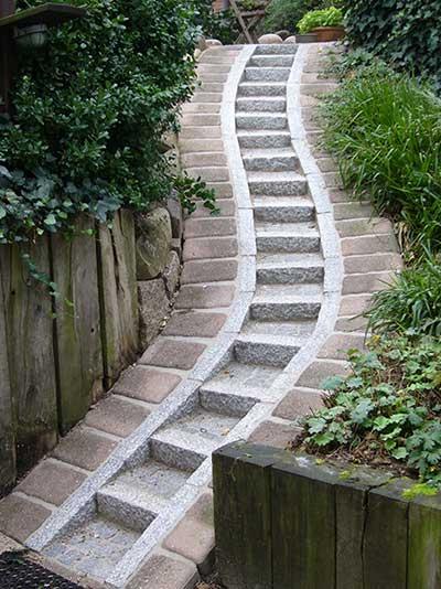 Schwungvoll: Treppe aus einer Verbindung von Granit und Betonsteinelementen.