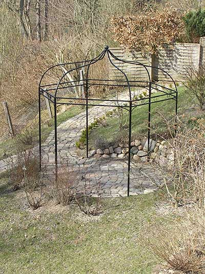 Romantisch: Ein dekorativer Pavillon mit Terrasse und Weg aus Natursteinen.