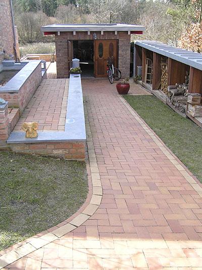 Verschiedene Ebenen: Wege und Terrasse aus melierten Ziegeln mit heller Kante.